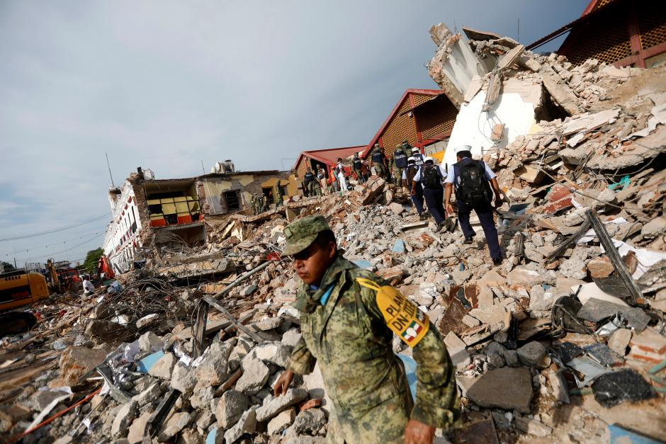 Soldiers work to remove the debris of a house destroyed in an earthquake that struck off the southern coast of Mexico late on Thursday, in Juchitan